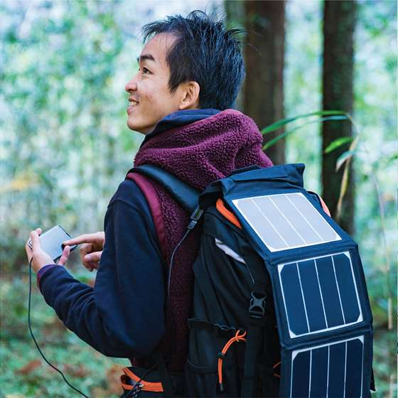 A man with a solar backpack on in the woods