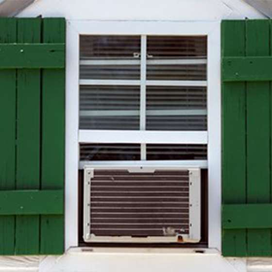 Image of a window air conditioning unit in the window of a house