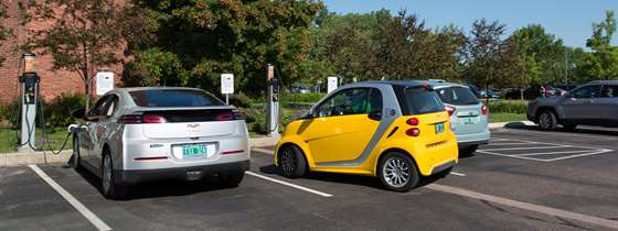 Two electric vehicles charging in a parking lot