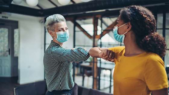 two women with masks for covid safety on touching elbows in a casual office setting