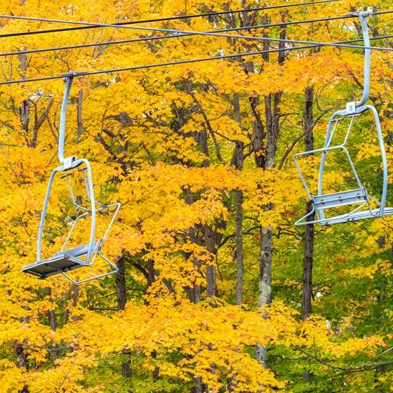 Two empty chair lifts in front of beautiful yellow foliages