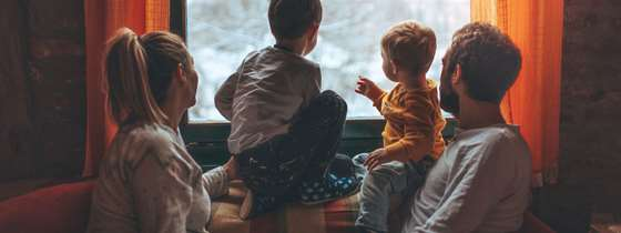 A family looks out the window at a snowy scene