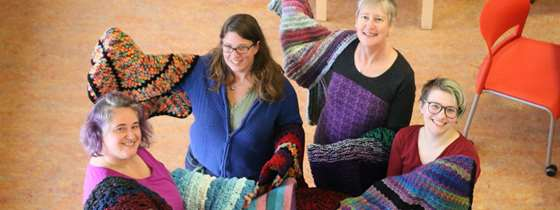 Image of several Efficiency Vermont employees holding blankets they knitted to give to customers.