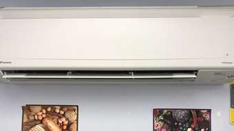 A heat pump at Rutland Community Cupboard on a wall above images of fruit, vegetables, and bread.