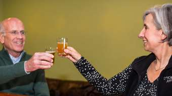 Peter Welch and Liz Gamache toast glasses of beer