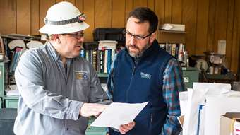Two men, one in a hard hat and one with an Efficiency Vermont vest, talk while looking at a document