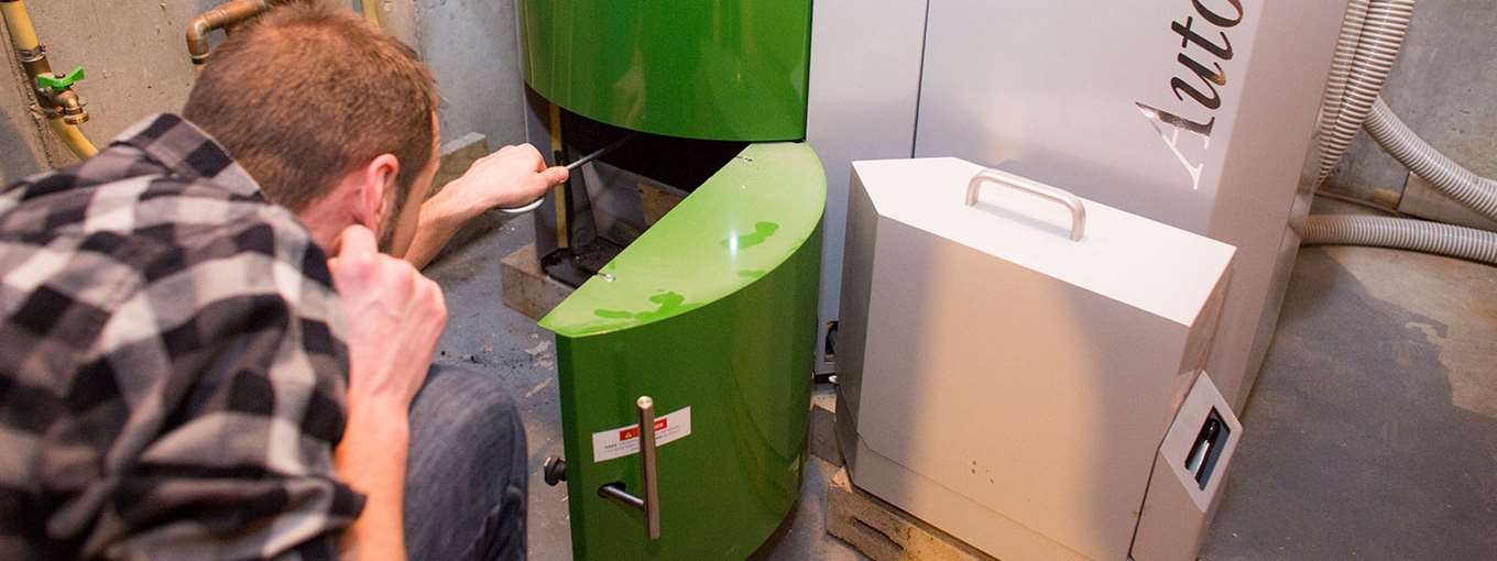 Kyle Emerson opens the door to his pellet boiler