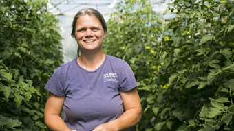 Christa Alexander smiles in one of her greenhouses