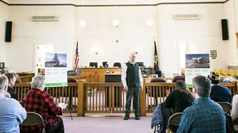 A man speaks to a group of people in a courtroom in Orleans County