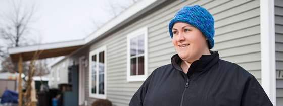 A woman stands outside her modular home