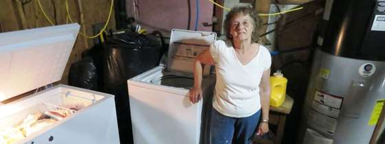 Gloria Powers stands next to her new efficient appliances