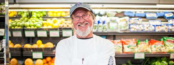 Photo of a man with glasses and a white beard smiling in front of refrigerator shelves containing grapefruit, lemons, limes, oranges, mushrooms, and green vegetables