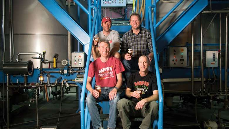 four men sitting on stairs in front of brewery equipment