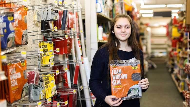 young woman holding foamm window seal in hardware store