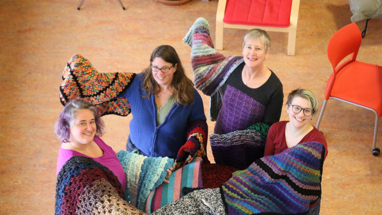 four women standing in a circle with knitted and crocheted blankets