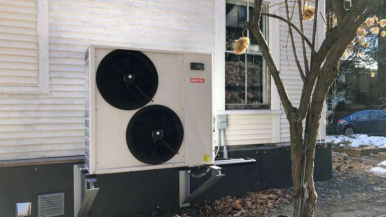 photo of heat pump compressor outside a home
