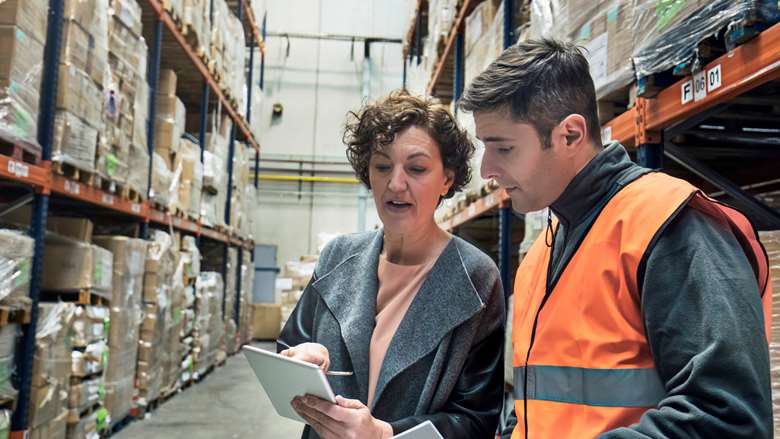 man and a woman looking at a tablet in a warehouse setting