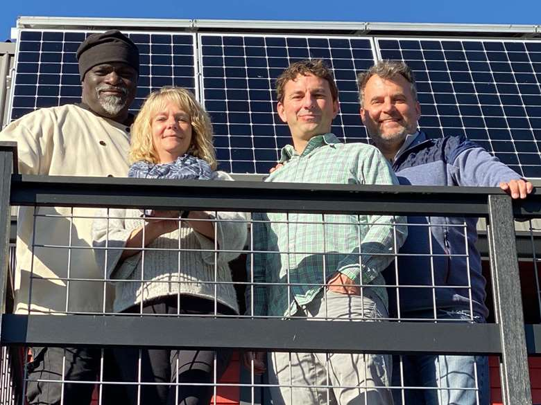Team in front of solar panels