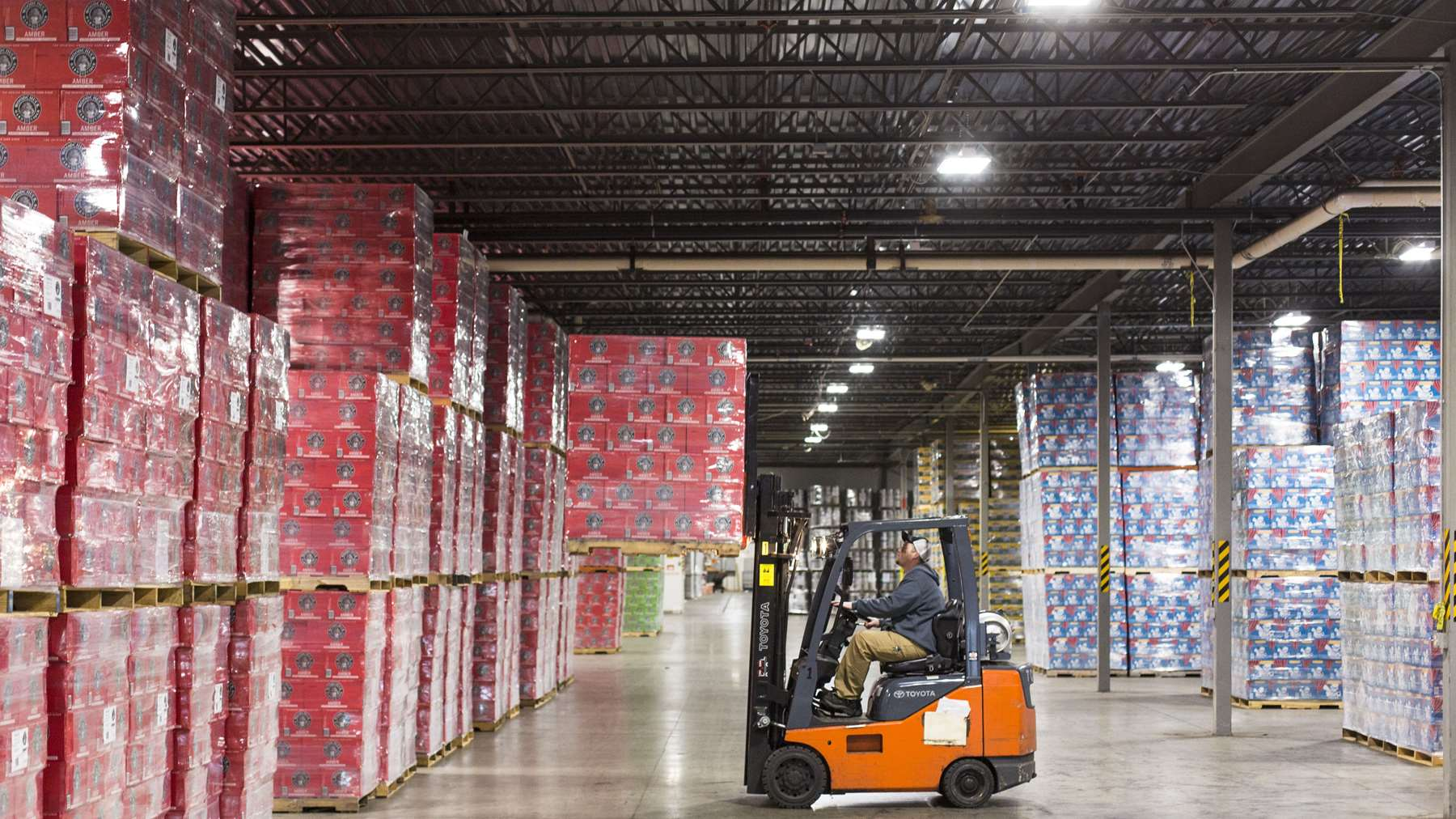 A man on a forklift moving towards stacks of boxed hard cider