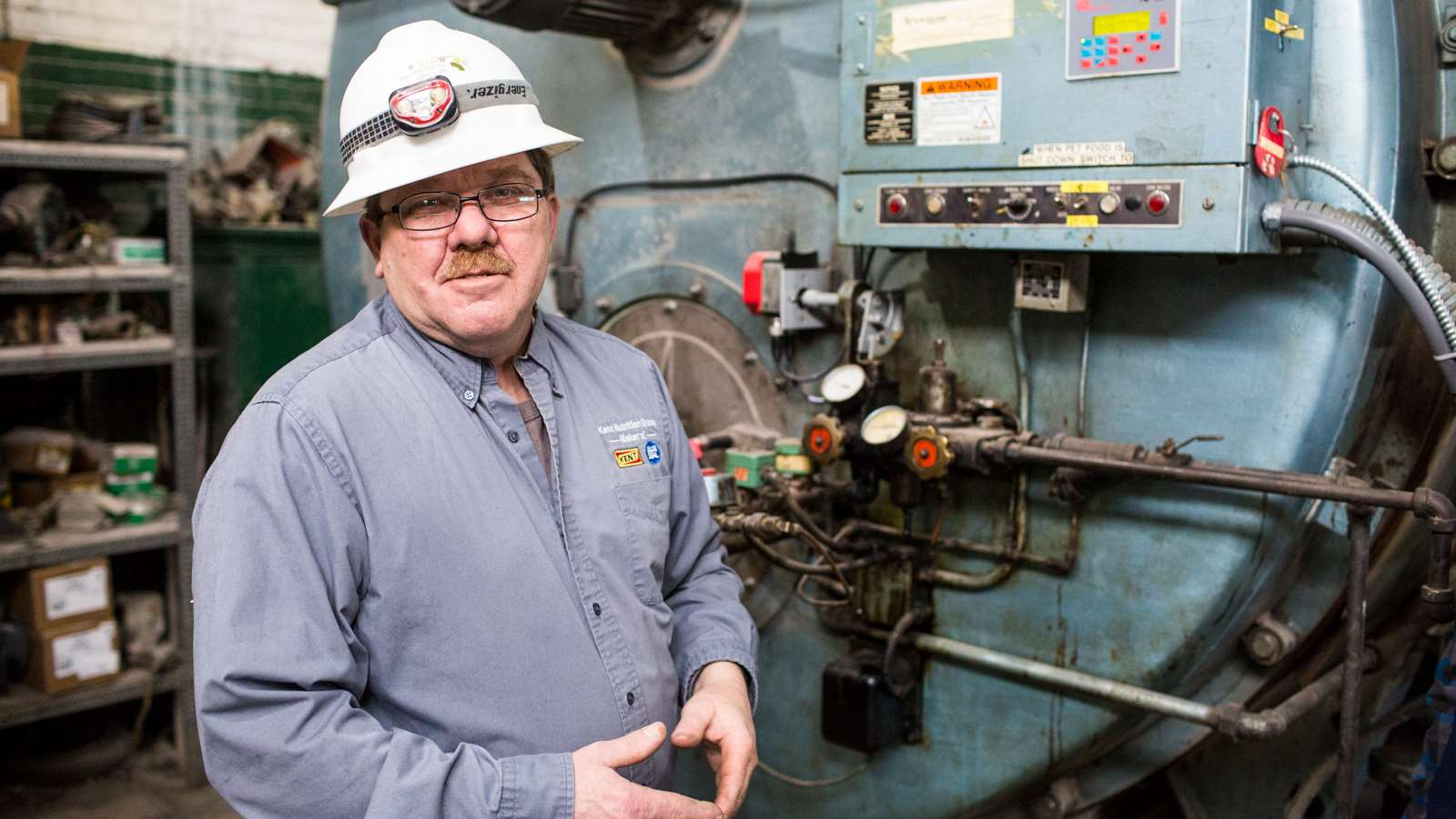 Blue Seal Maintenance Manager Dan Turcotte in front of boiler controls that have saved the company $53,800 per year.