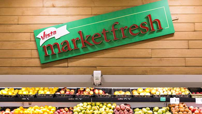"large rectangular green sign, reads ""Vista Market fresh"" hangs above wicker baskets filled with fruit"